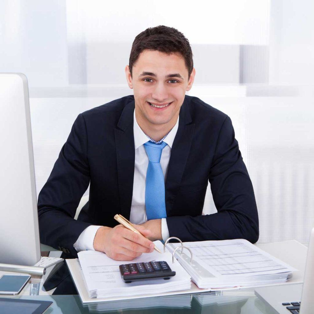 young man in black suit sitting at desk with computer pen open book and calculator