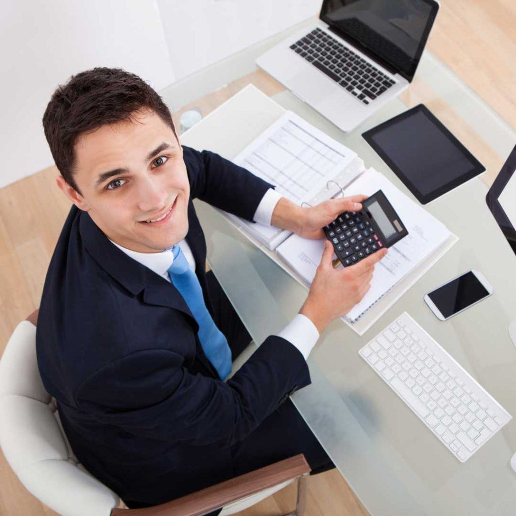 man in dark suit with blue tie sitting at desk with calculator computer phone and tablet looking up