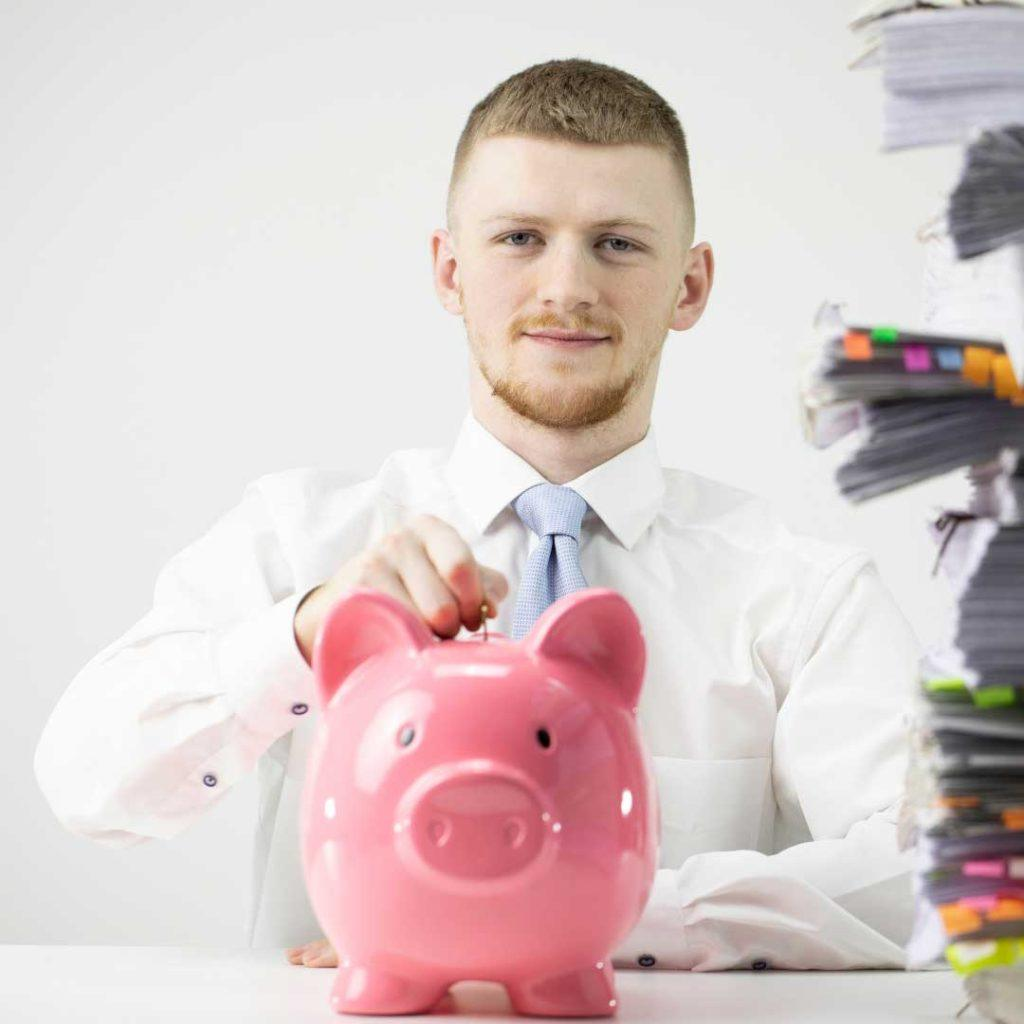 man in white shirt placing money in pink piggy bank