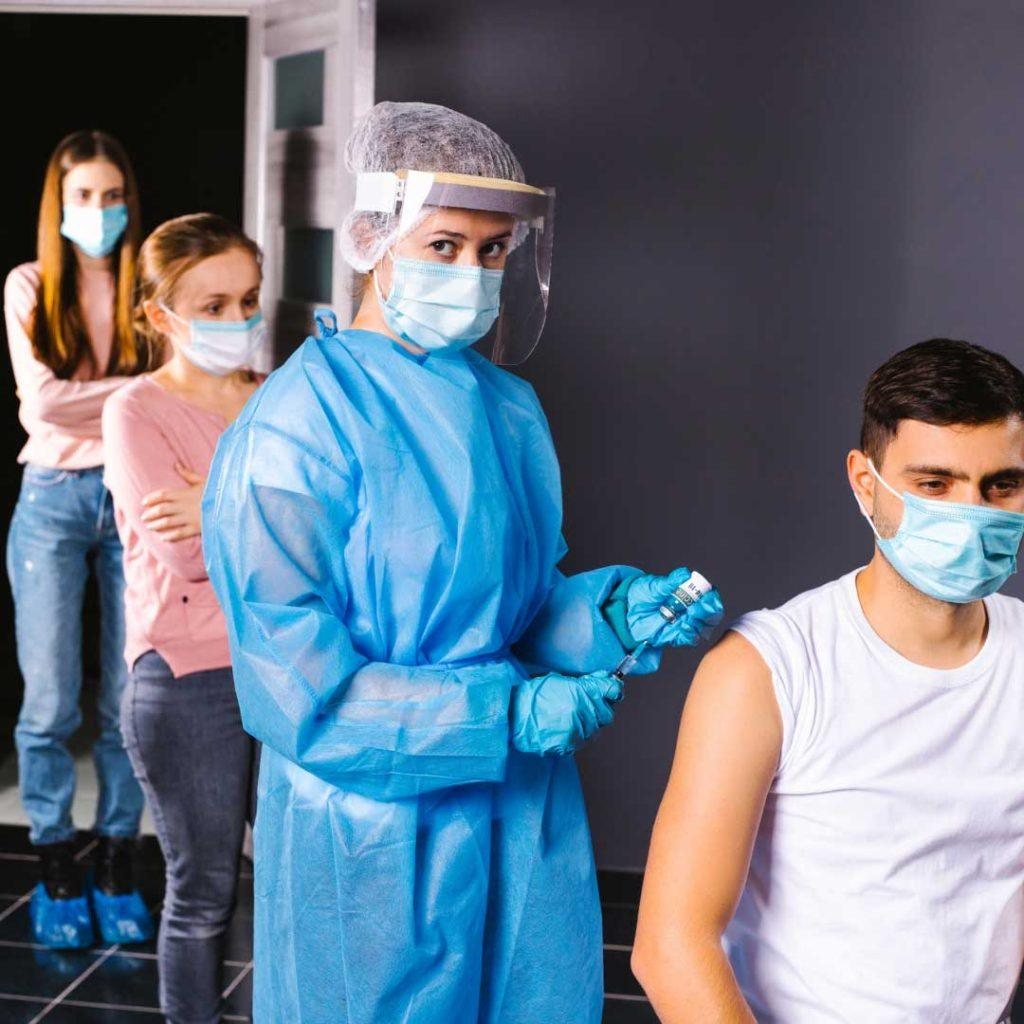 lineup of people wearing masks including woman in blue gown wearing face shield