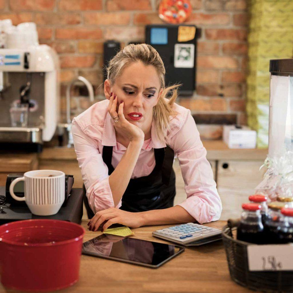 woman in coffee shop leaning on counter with tablet and calculator