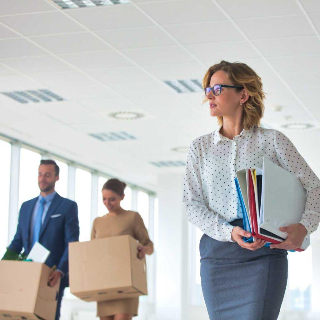 business woman holding binders walking in office with two people holding boxes in the background