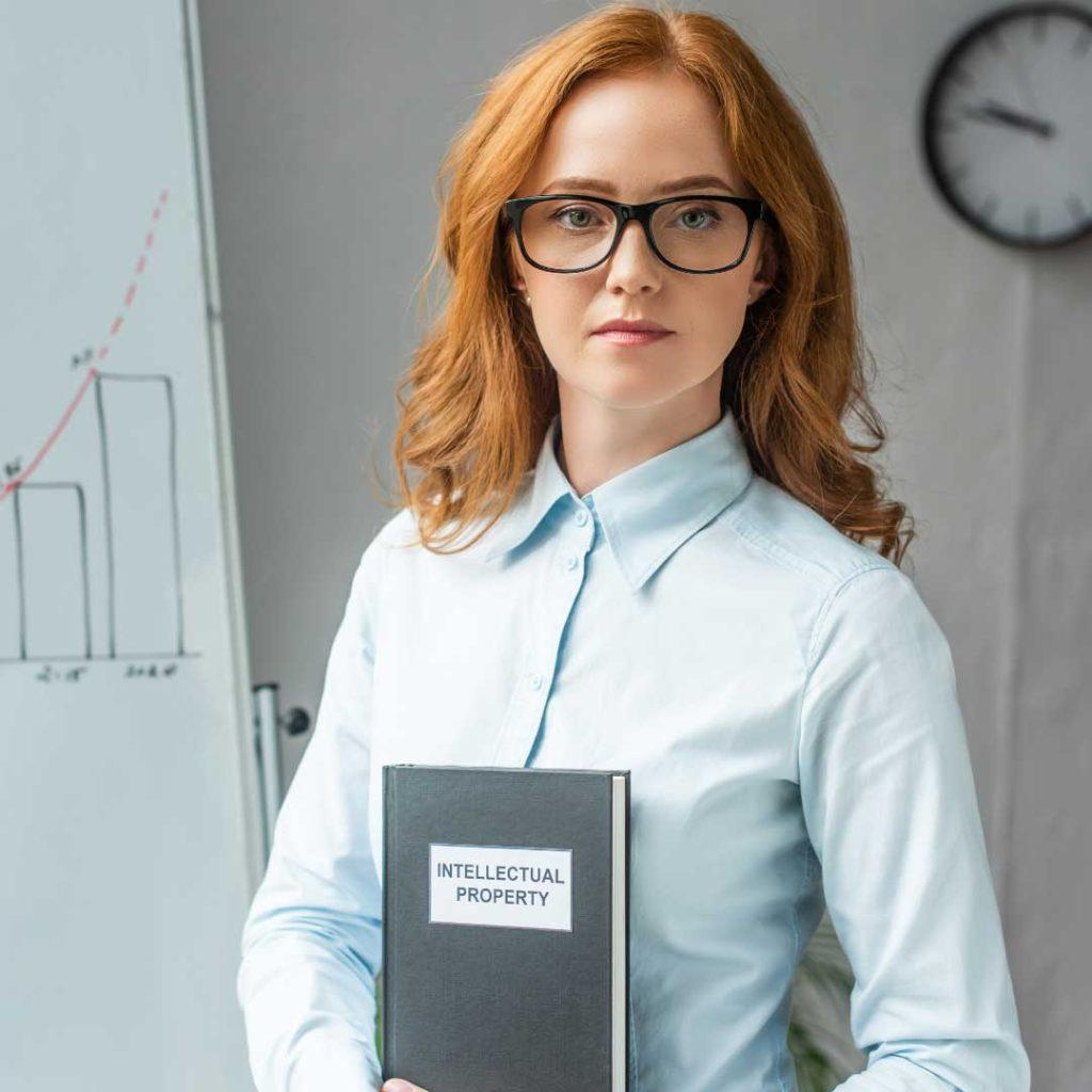 young woman with red hair holding intellectual property book
