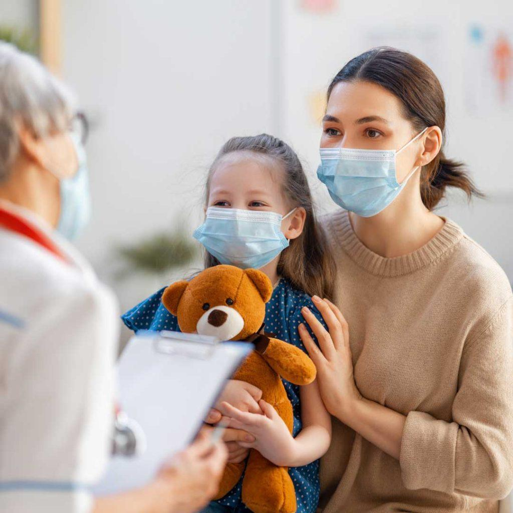 mom and daughter holding stuffed bear standing in front of doctor with clipboard