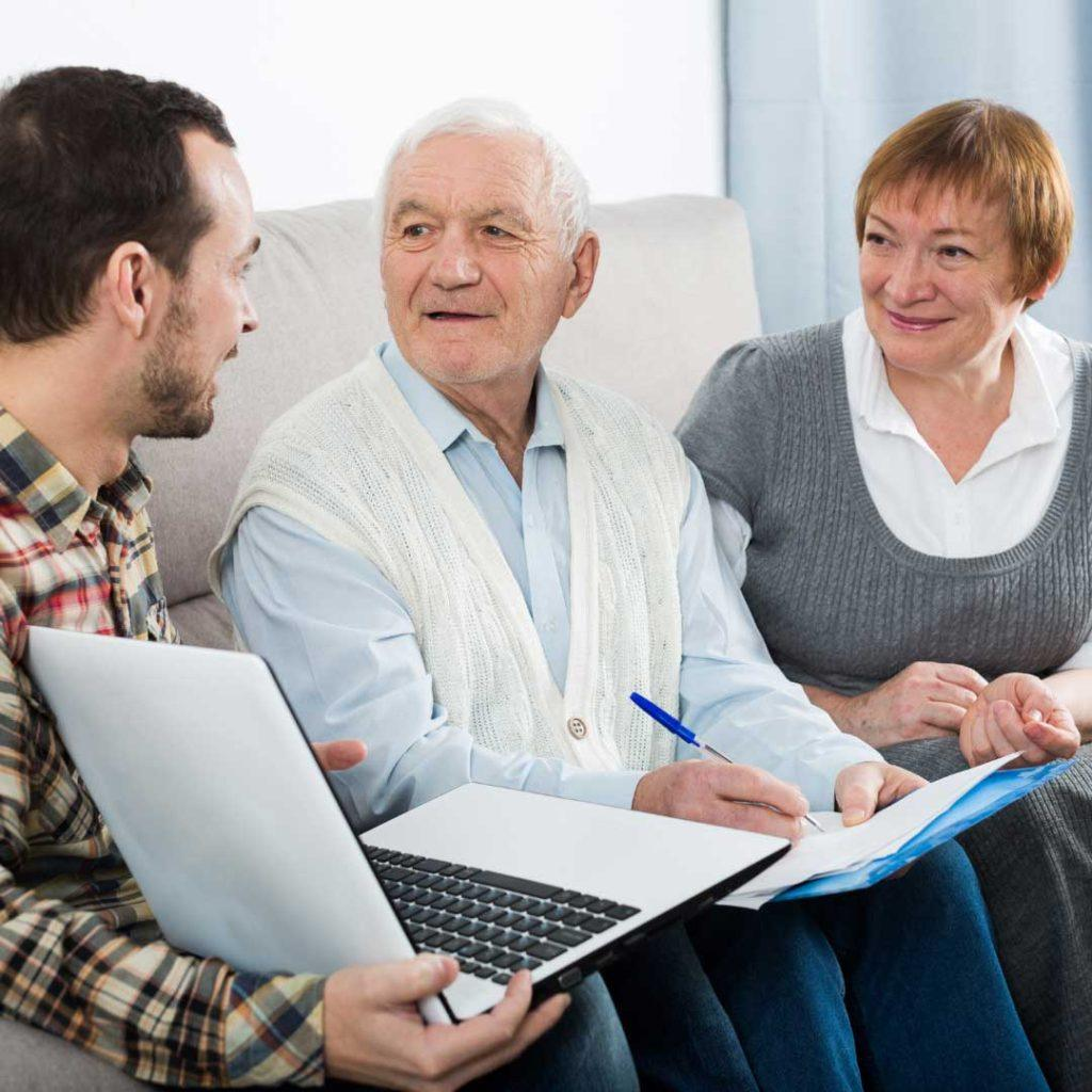 young man with laptop sitting beside older couple with pen and paper