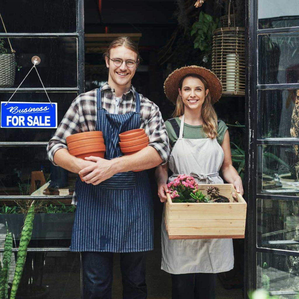 young man and woman holding flowers in front of building with business for sale sign