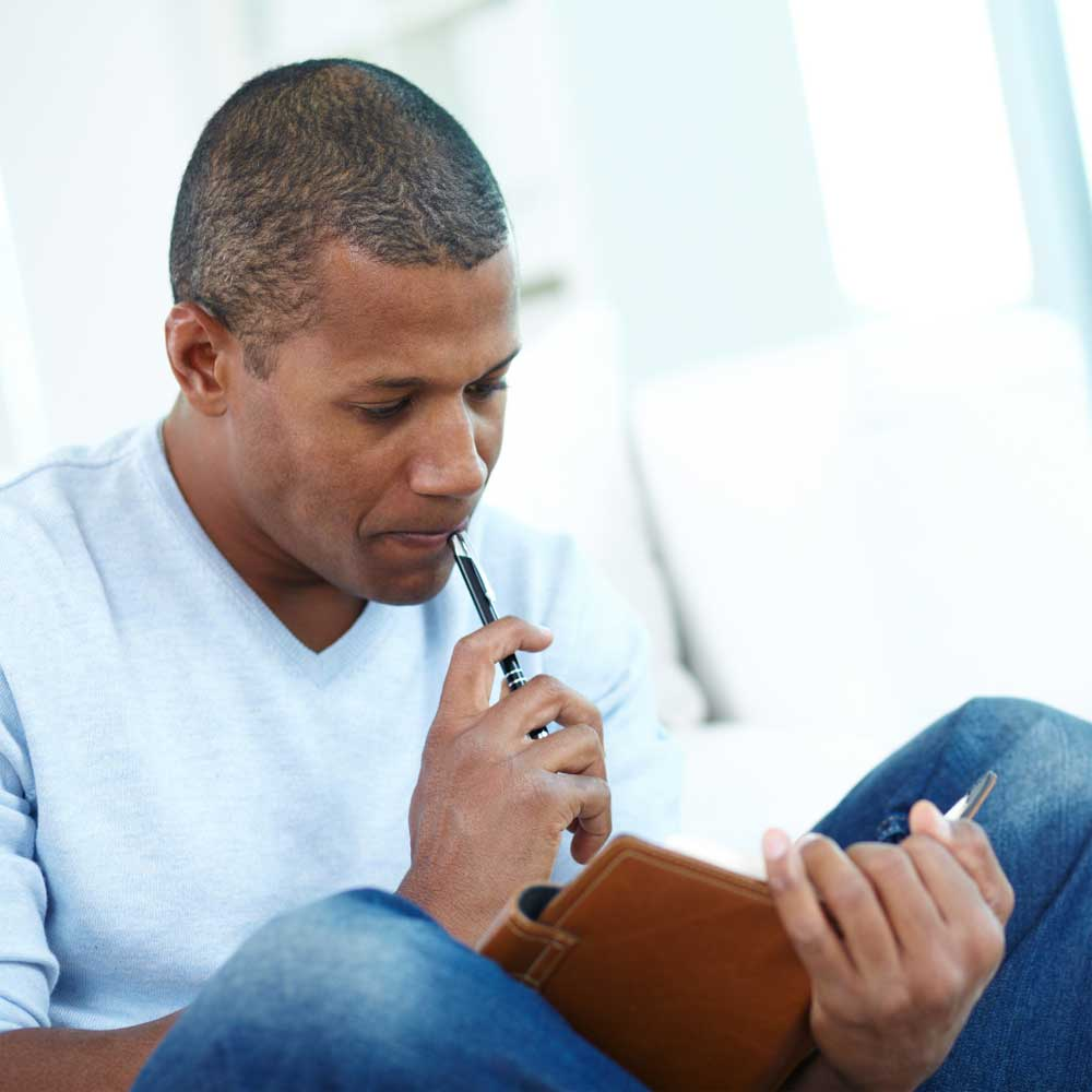 man holding a notebook with a pen in hand thinking about what to write