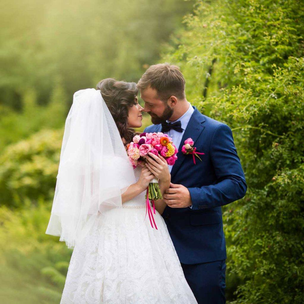 groom and bride in a garden looking at each other