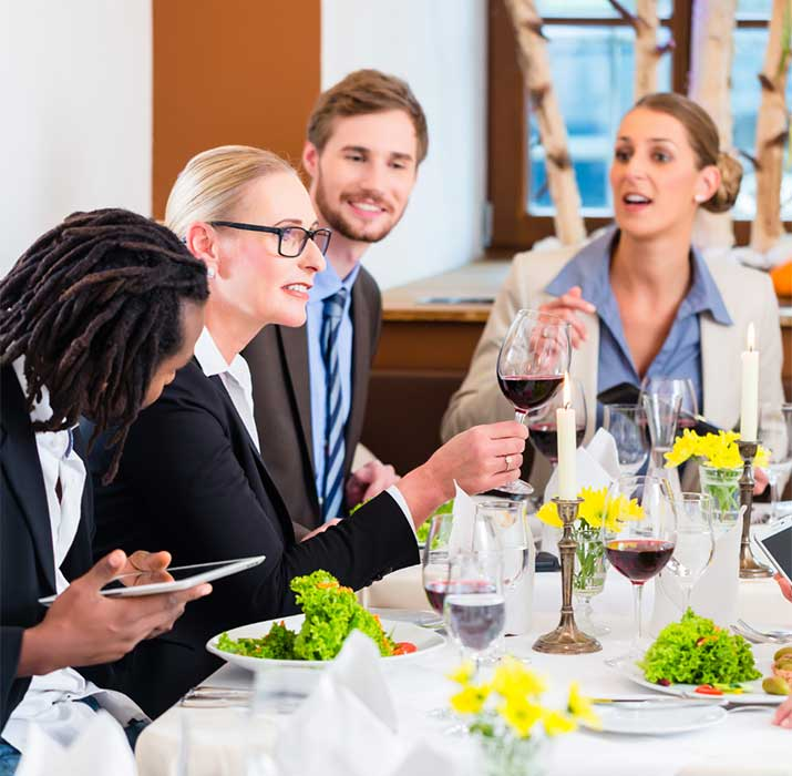 four people smiling and talking with one another over meal