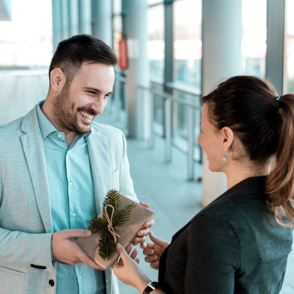 man smiling while handing gift to a woman