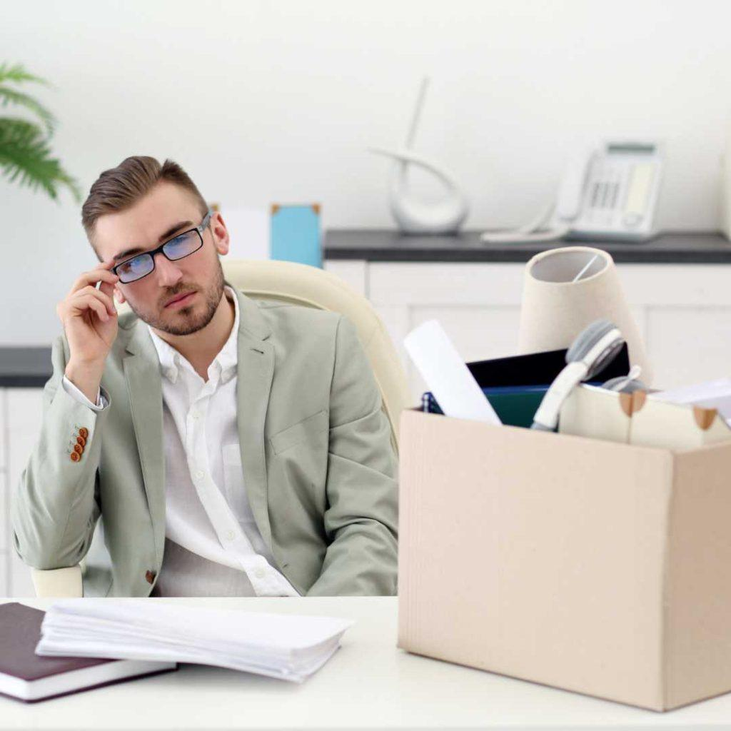 man wearing glasses with box of his stuff on his table